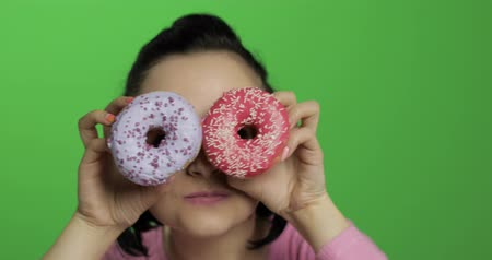изолированные на белом : Happy beautiful young girl on a chroma key background having fun with donuts. Cute woman in a pink shirt posing with donuts closes her eyes and smiling. Making faces. Close-up shot