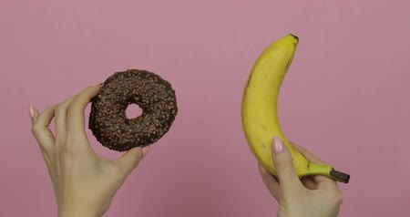 rosquinhas : Choice donut against banana. Starting healthy eating or junk food. Girl hands on a pink background holds donut in one hand and banana on other
