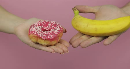 kobliha : Choice donut against banana. Starting healthy eating or junk food. Hands on a pink background holds donut in one hand and banana on other Dostupné videozáznamy