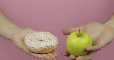 пончик : Choice donut against apple. Starting healthy eating or junk food. Hands on a pink background holds donut in one hand and apple on other Стоковые видеозаписи