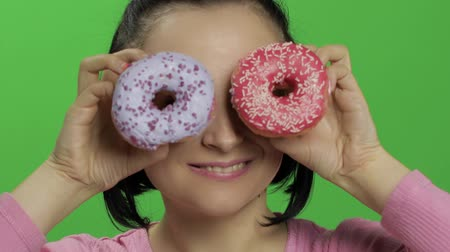 пончик : Happy beautiful young girl on a chroma key background having fun with donuts. Cute woman in a pink shirt posing with donuts closes her eyes and smiling. Making faces. Close-up shot