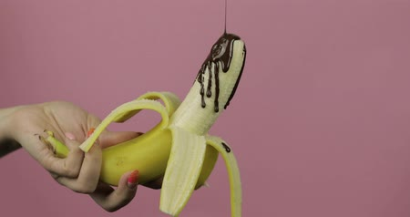 очищенные : Pouring a banana with melted dark chocolate syrup. A peeled banana gets covered in chocolate cream. Pink background