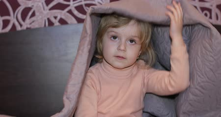 hides : Little cheerful girl hides under a blanket and watching TV. Sweet, adorable child having fun on the bed under a coverlet. Concept of kids sleep, care or childhood Stock Footage