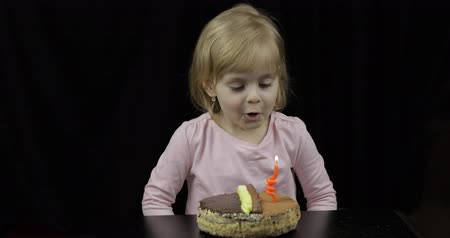 explodindo : Little girl blows out red festive candle on birthday chocolate cake on black background. Happy 4 years child. Sweet, cute blonde hair girl Stock Footage