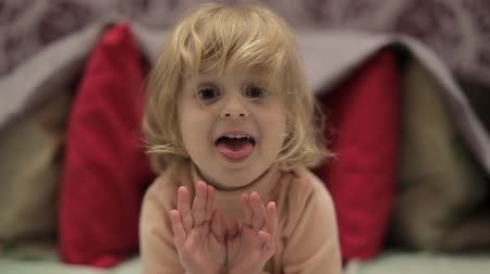 hides : Little cheerful girl showing tongue. Sweet, adorable child having fun on the bed. Concept of kids at home, childhood