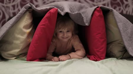 hides : Little cheerful girl hides under blanket and pillows on the bed. Sweet, adorable child having fun under a coverlet. Concept of hiding place, homemade house Stock Footage