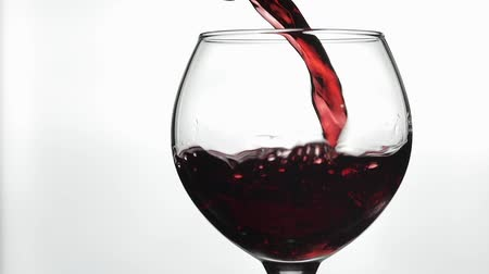 şarap kadehi : Wine. Red wine pouring in wine glass over white background. Rose wine pour into a glass. Close up shot. Slow motion Stok Video