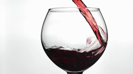 bordeaux : Wine. Red wine pouring in wine glass over white background. Rose wine pour into a glass. Close up shot. Slow motion Filmati Stock