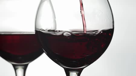 выстрел : Wine. Red wine pouring in wine glass over white background. Rose wine pour into a drinking glass. Close up shot. Slow motion
