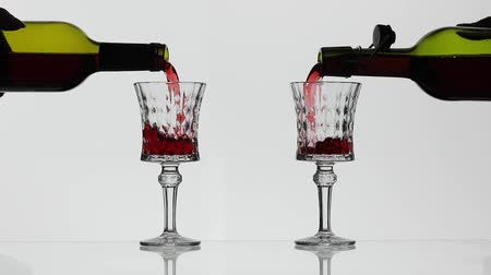 şarap kadehi : Wine. Red wine pouring in two wine glasses over white background. Rose wine pour from the bottle. Slow motion