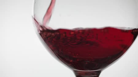 каберне : Wine. Red wine pouring in wine glass over white background. Rose wine pour into a glass. Close up shot. Slow motion Стоковые видеозаписи