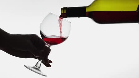 Бордо : Wine. Red wine pouring in wine glass over white background. Rose wine pour from the bottle. Slow motion Стоковые видеозаписи