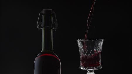 ボルドー : Wine. Red wine pouring in wine glass over black background. Rose wine pour into a drinking glass. Silhouette. Close up shot. Slow motion
