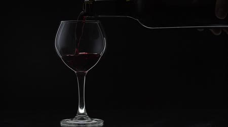 bordeaux : Wine. Red wine pouring in wine glass over black background. Rose wine pour from the bottle. Silhouette. Close up shot. Slow motion