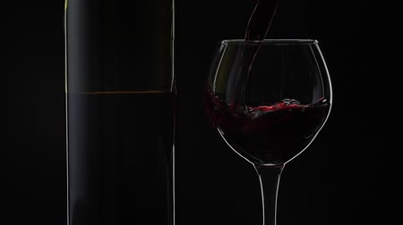 degustation : Wine. Red wine pouring in wine glass over black background. Rose wine pour into a drinking glass. Silhouette. Close up shot. Slow motion