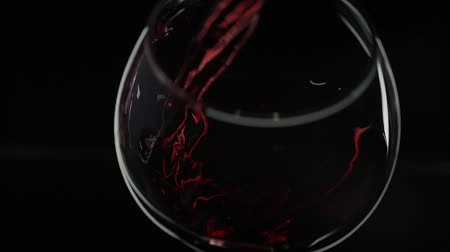 şarap kadehi : Wine. Red wine pouring in wine glass over black background. Rose wine pour into a drinking glass. Silhouette. Close up shot. Slow motion