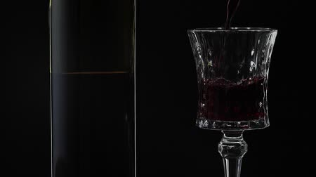 tasting : Wine. Red wine pouring in wine glass over black background. Rose wine pour into a drinking glass. Silhouette. Close up shot. Slow motion