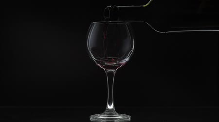 Бордо : Wine. Red wine pouring in wine glass over black background. Rose wine pour from the bottle. Silhouette. Close up shot. Slow motion