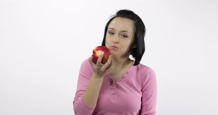 espectador : Young beautiful woman eating big red apple and says yum. Girl takes first bite and then offer bite to viewer and saying Wanna bite. Tastes an apple. Healthy nutrition. Original audio Vídeos