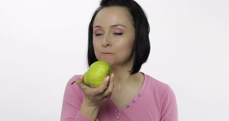 yum yum : Young beautiful woman eating big, fresh, juicy, green pear and says yum. Girl takes first bite and then offer bite to viewer and saying Wanna bite. Tastes a pear. Healthy nutrition. Original audio Stock Footage