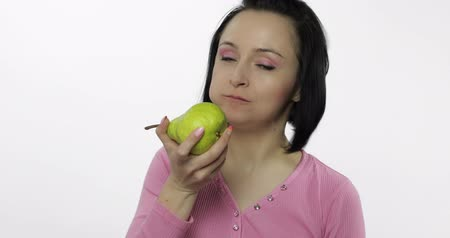 espectador : Young beautiful woman eating big, fresh, juicy, green pear and says yum. Girl takes first bite and then offer bite to viewer and saying Wanna bite. Tastes a pear. Healthy nutrition. Original audio Vídeos