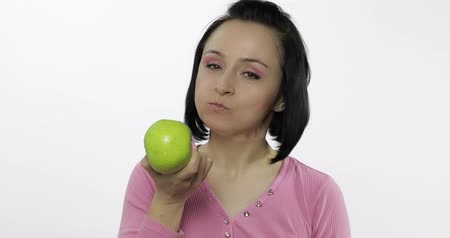 espectador : Young beautiful woman eating big green apple and says yum. Girl takes first bite and then offer bite to viewer and saying Wanna bite. Tastes an apple. Healthy nutrition. Original audio