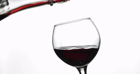 bordeaux : Wine. Red wine pouring in wine glass over white background. Rose wine pour from the bottle. Close up shot
