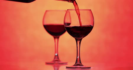 Бордо : Woman puts a wine glass. Red wine pouring in glass over orange background. Rose wine, red juice pour from the bottle Стоковые видеозаписи
