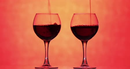 каберне : Wine. Red wine pouring in two wine glasses over orange background. Rose wine, red juice pour into a glass