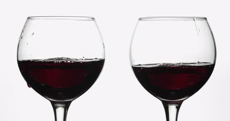 каберне : Wine. Red wine pouring in two wine glasses over white background. Rose wine, red juice pour into a glass. Close up shot