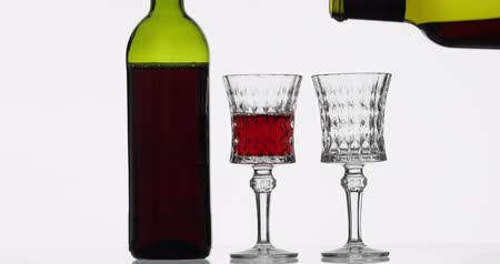 каберне : Wine. Red wine pouring in two wine glasses over white background. Rose wine pour from the bottle Стоковые видеозаписи