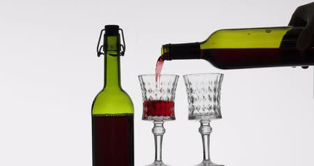 Бордо : Wine. Red wine pouring in two wine glasses over white background. Rose wine pour from the bottle Стоковые видеозаписи