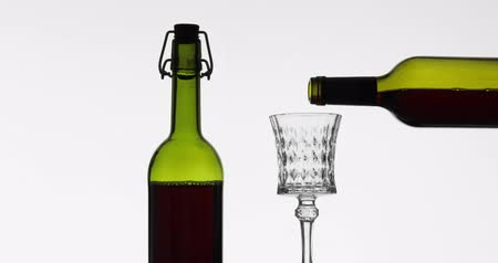 sommelier : Wine. Red wine pouring in wine glass over white background. Rose wine pour from the bottle