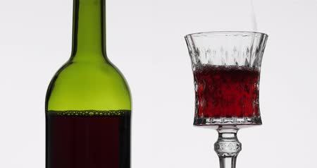 Бордо : Wine. Red wine pouring in wine glass over white background. Rose wine pour into a glass. Close up shot Стоковые видеозаписи