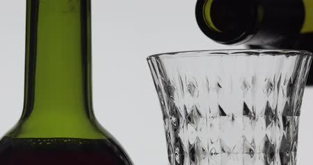 Бордо : Wine. Red wine pouring in wine glass over white background. Rose wine pour from the bottle. Close up shot