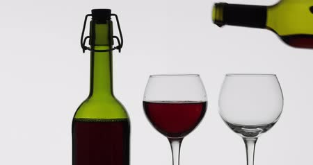 bordeaux : Wine. Red wine pouring in two wine glasses over white background. Rose wine pour from the bottle Filmati Stock