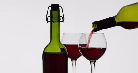 tasting : Wine. Red wine pouring in wine glass over white background. Rose wine pour from the bottle