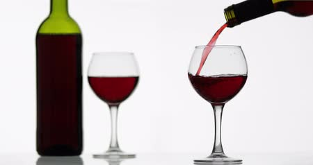 Бордо : Wine. Red wine pouring in wine glass over white background. Rose wine pour from the bottle