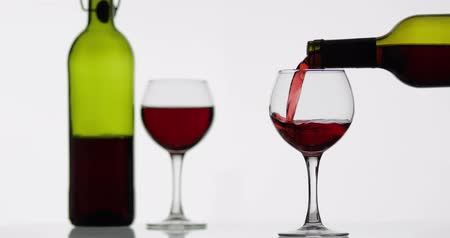 bordeaux : Wine. Red wine pouring in wine glass over white background. Rose wine pour from the bottle