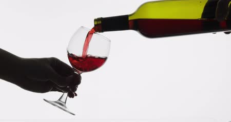 sommelier : Wine. Red wine pouring in wine glass over white background. Rose wine pour from the bottle. Close up shot