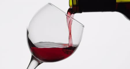 şarap kadehi : Wine. Red wine pouring in wine glass over white background. Rose wine pour from the bottle. Close up shot