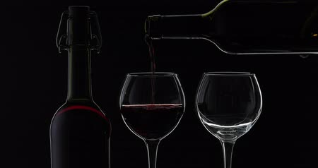 Бордо : Wine. Red wine pouring in two wine glasses over black background. Rose wine pour from the bottle. Silhouette. Close up shot