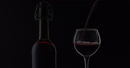 カベルネ : Wine. Red wine pouring in wine glass over black background. Rose wine pour into a glass. Silhouette. Close up shot