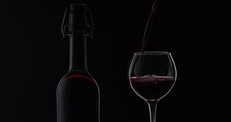 bordeaux : Wine. Red wine pouring in wine glass over black background. Rose wine pour from the bottle. Silhouette. Close up shot
