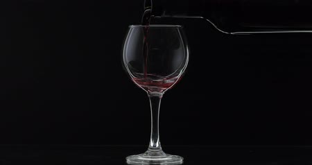 Бордо : Wine. Red wine pouring in wine glass over black background. Rose wine pour from the bottle. Silhouette Стоковые видеозаписи
