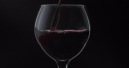 şarap kadehi : Wine. Red wine pouring in wine glass over black background. Rose wine pour into a glass. Silhouette. Close up shot