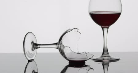 shattering : Detail shot of broken wine glass with red wine which is laying on the wet surface and shaking. White background Stock Footage