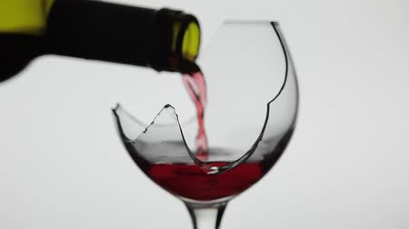 shattering : Wine. Red wine pouring in broken wine glass on the white background. Rose wine pour from the bottle. Close up shot. Slow motion Stock Footage