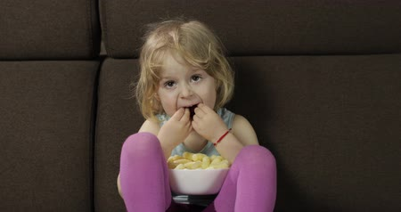 puffs : Beautiful little blonde girl sitting on a sofa at home and eating corn puffs. Cute child smiling and taste puffcorns. Inside. Childrens meal
