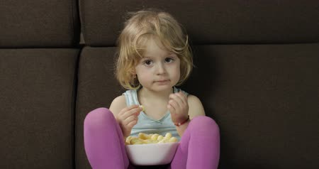 chroupat : Beautiful little blonde girl sitting on a sofa at home and eating corn puffs. Cute child watching tv and taste puffcorns. Inside. Childrens meal